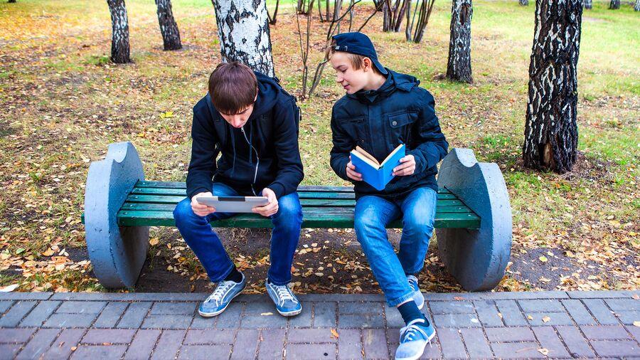 To børn læser på iPad og i bog på en bænk